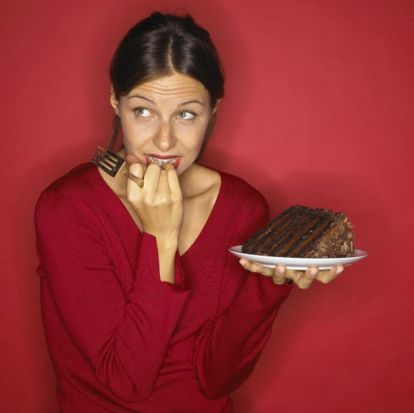 Conflicted woman holding chocolate cake